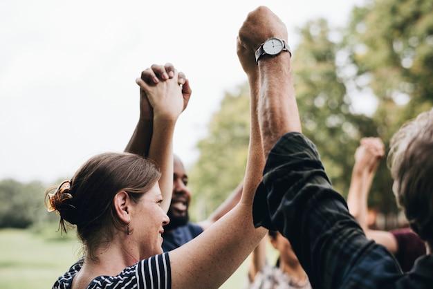 Diversas pessoas felizes de mãos dadas no parque Foto gratuita