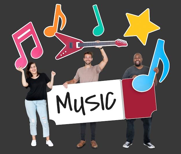 Diversas pessoas felizes segurando ícones da música Foto gratuita