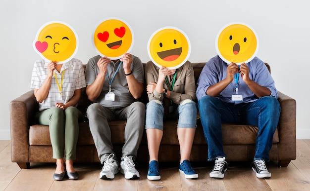 Diversas pessoas sentadas e cobrindo o rosto com placas de emojis Foto Premium
