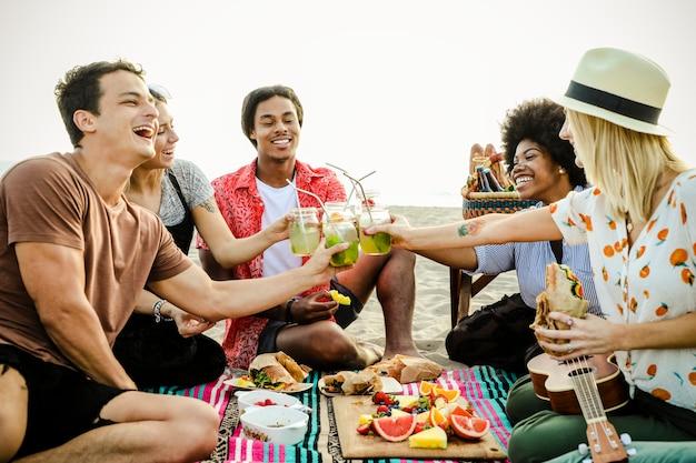 Diversos amigos desfrutando de um piquenique na praia Foto Premium