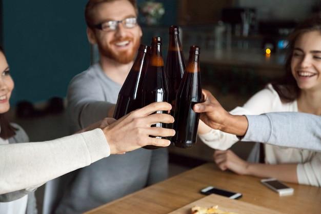 Diversos amigos tinindo garrafas de cerveja artesanal no pub, cheers conceito Foto gratuita