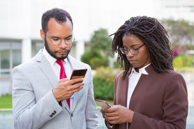 Diversos colegas de trabalho usando smartphones Foto gratuita