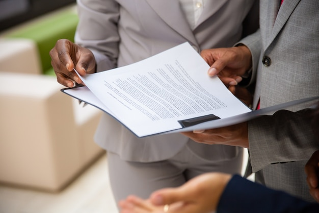 Diversos parceiros de negócios lendo contrato juntos Foto gratuita