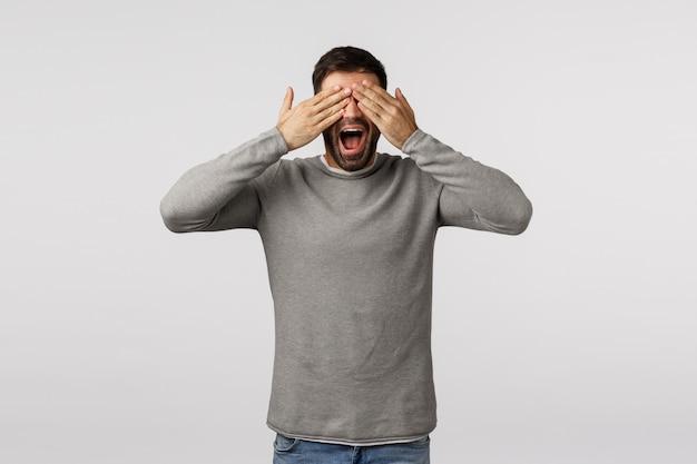Divertido e despreocupado, feliz bonitão barbudo de suéter cinza, fechar os olhos com as palmas das mãos e sorrir imaginando, aguardando uma surpresa agradável, quero ver presente, brincar de esconde-esconde, esconder e procurar Foto Premium