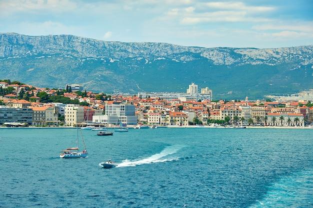 Dividir o porto da cidade do convés superior de uma grande balsa marítima. mar, barcos de passageiros, navios, casas históricas. Foto Premium