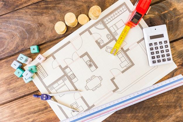 Divisor, régua, blocos de matemática, calculadora, moedas empilhadas e blueprint na mesa de madeira Foto gratuita