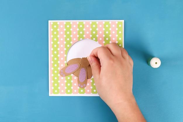 Diy cartões de páscoa de papel. cartões de volume com um coelho, ovo sobre fundo azul. 3d. Foto Premium