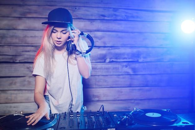 Dj bonito mulher se divertindo tocando música na festa do clube Foto gratuita