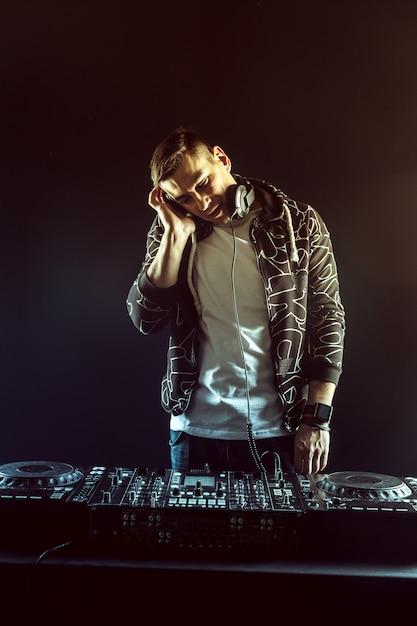 Dj mistura de música na mesa de mixagem em fundo escuro Foto Premium
