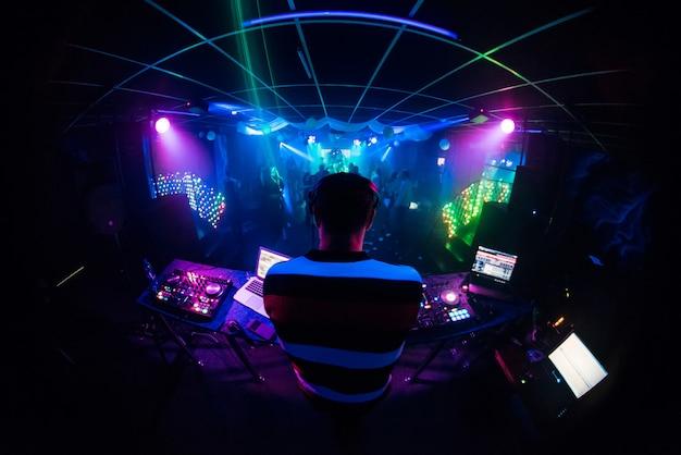 Dj mistura música em uma boate com pessoas dançando Foto Premium