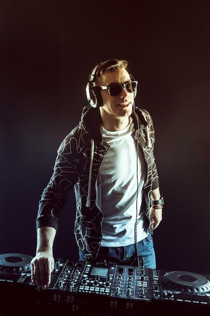 Dj mistura música no misturador no escuro Foto Premium