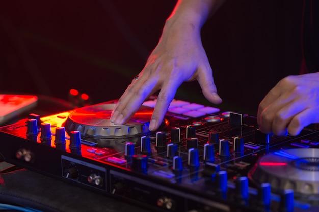 Dj mixagem de faixas em um mixer em uma boate. Foto Premium