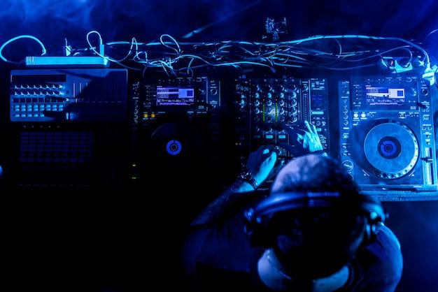 Dj tocando house e música techno em um clube noturno. misturando e controlando a música. Foto Premium