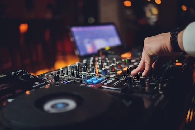 Djs entregam o laptop e o console de mixagem controlando as configurações de som Foto Premium