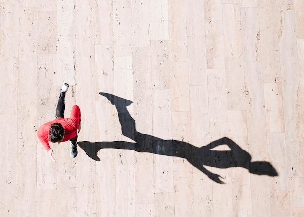 Do desportista acima, correndo no pavimento Foto gratuita