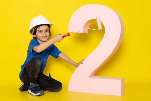 Doce adorável menino bonitinho na camiseta azul e calça escura perto número figura na parede amarela Foto gratuita