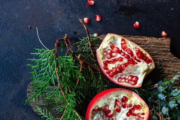 Doce de fruta vermelha de romã na mesa e um galho de árvore de natal verde Foto Premium