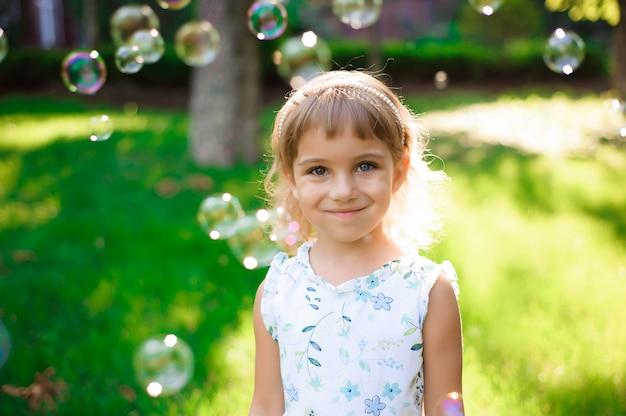 Doce, feliz, sorridente menina de cinco anos deitado em uma grama Foto Premium