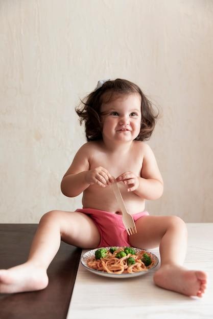 Doce menina brincando com espaguete Foto gratuita