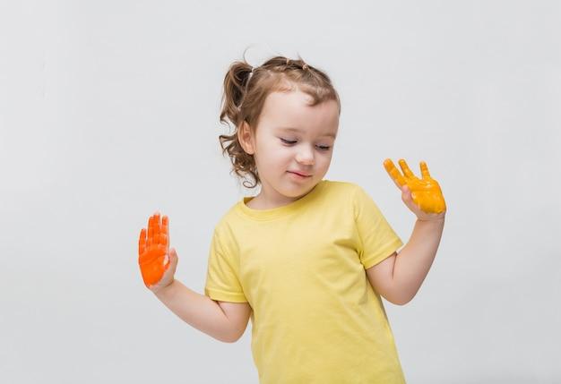 Doce menina com rabos de cavalo em uma camiseta amarela com as mãos na pintura. aprendendo a desenhar Foto Premium