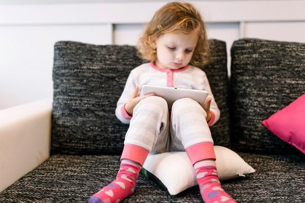 Doce menina com tablet no sofá Foto gratuita