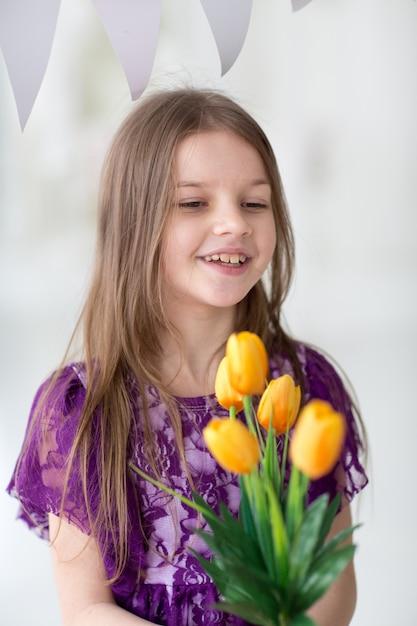 Doce menina de cabelos escuros no vestido roxo em estúdio com tulipas amarelas Foto Premium