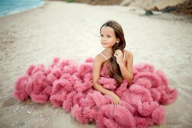 Doce menina de vestido rosa na praia Foto Premium