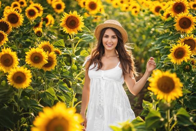 Doce mulher em um vestido branco andando em um campo de girassóis Foto Premium