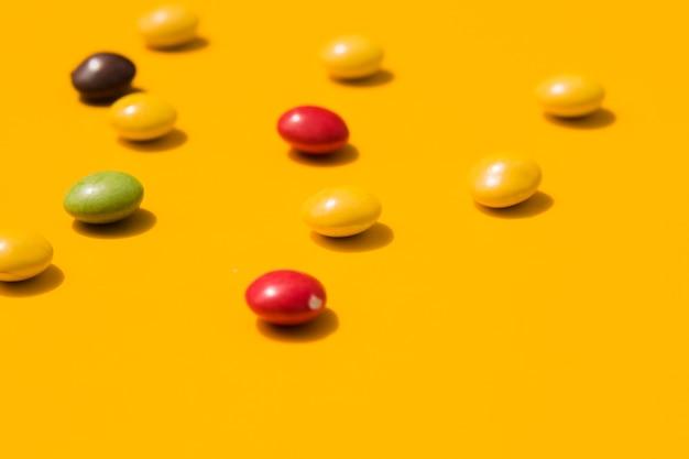 Doces coloridos em pano de fundo amarelo Foto gratuita