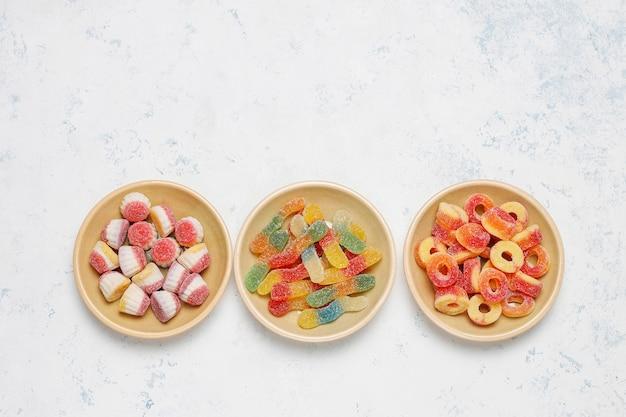 Doces coloridos, geléia, marshmallow na superfície da luz. vista superior com espaço de cópia Foto gratuita