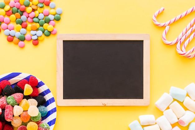 Doces coloridos, hortelã e marshmallow no pano de fundo amarelo Foto gratuita