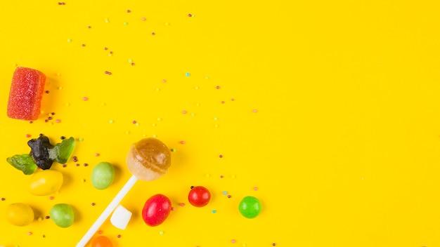 Doces coloridos vívidos no fundo amarelo Foto gratuita