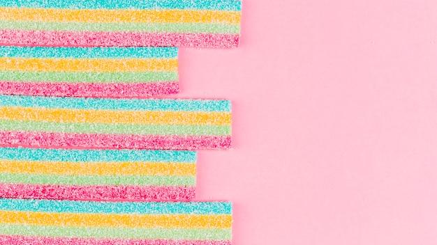 Doces de açúcar listrado colorido em fundo rosa Foto gratuita