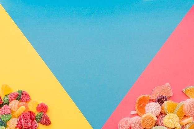 Doces de geleia doce colorido sobre o fundo triangular amarelo e rosa Foto gratuita