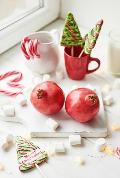 Doces de natal romã, leite, marshmallows, doces pela janela Foto Premium