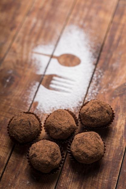 Doces de trufa de chocolate caseiros com cacau em pó, perto da forma de colher e garfo em pó de açúcar Foto gratuita