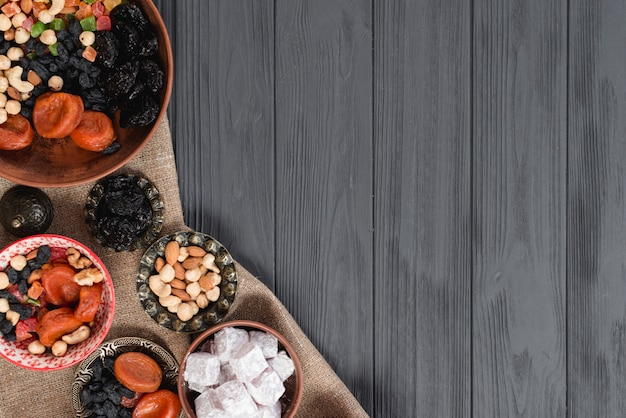 Doces do ramadã turca e frutas secas na mesa de madeira preta Foto gratuita