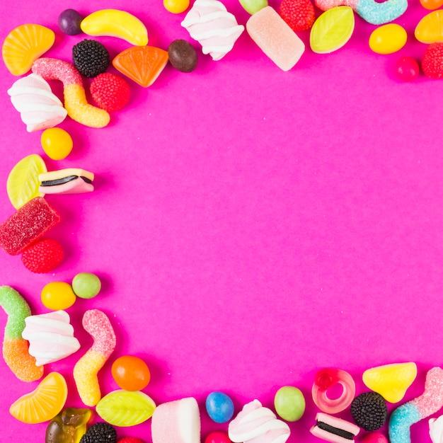 Doces doces com várias formas no fundo rosa Foto gratuita