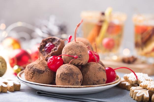 Doces doces de natal em cima da mesa de sobremesa. bolas de biscoito com cereja - loli pop ou bolo pop. decoração de ano novo e bebida de cidra de maçã. conceito feliz holidey Foto Premium