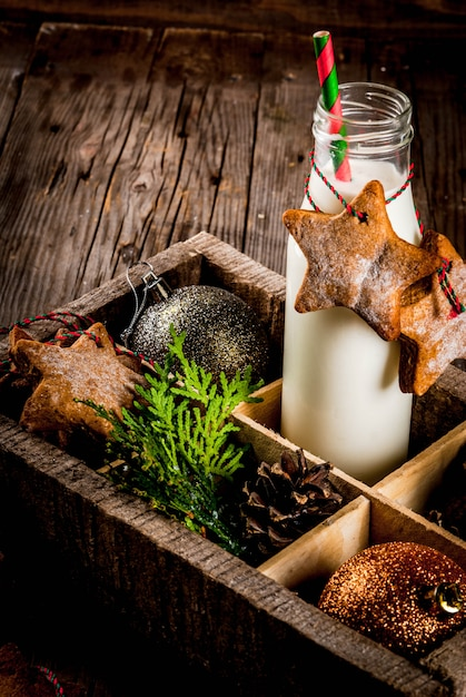Doces e guloseimas de natal, garrafa com leite para o papai noel com biscoitos estrela de gengibre Foto Premium