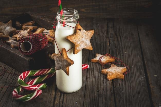 Doces e guloseimas, garrafas de leite para o papai noel com biscoitos estrela de gengibre com corda de decoração, de madeira velha, Foto Premium