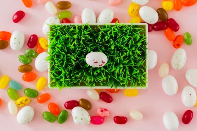 Doces e ovos em volta do pote com grama Foto gratuita
