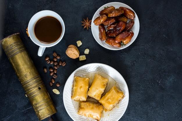 Doces orientais com frutas de datas e xícara de café Foto gratuita