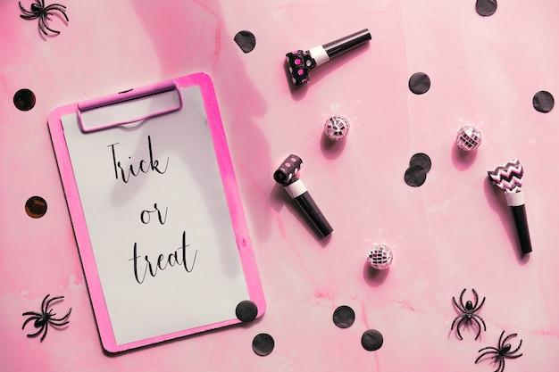 Doces ou travessuras texto na área de transferência em fundo rosa decoração de festa - confete de papel, criadores de ruído, aranhas de plástico preto. Foto Premium