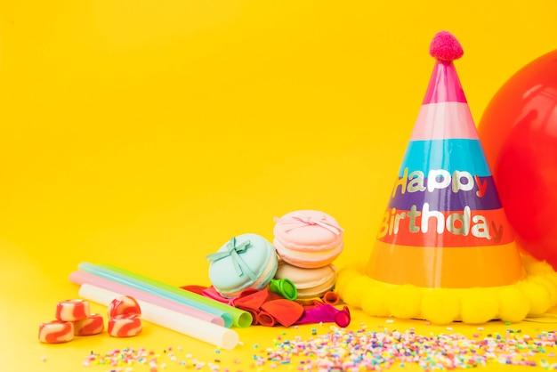 Doces; palha; balão esvaziado; macarons e chapéu de papel em fundo amarelo Foto gratuita