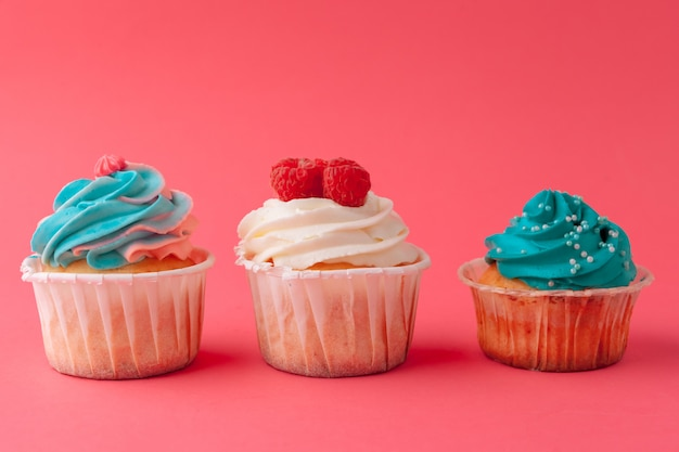 Doces saborosos cupcakes na rosa close-up Foto Premium