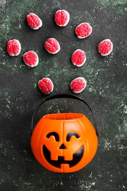 Doces terríveis (cérebros) para o halloween na abóbora decorativa em um fundo escuro Foto Premium