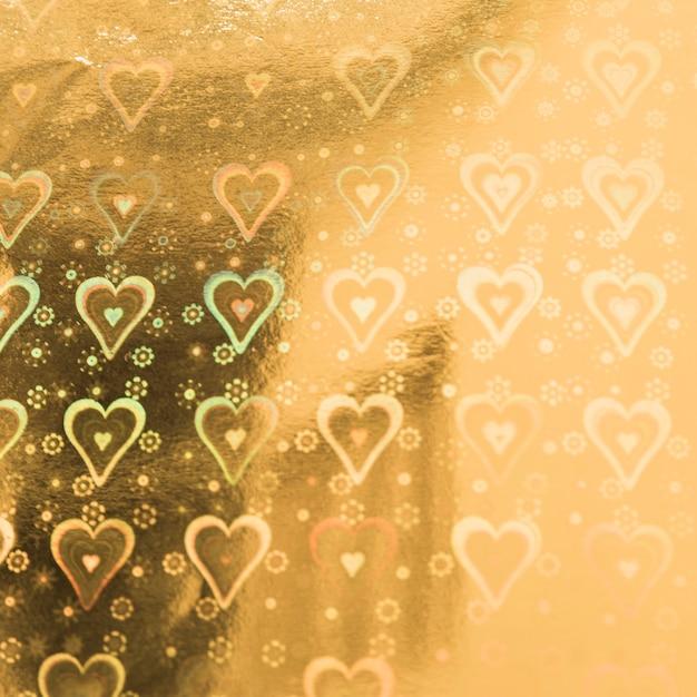 Docinho de ouro com padrão de corações Foto gratuita