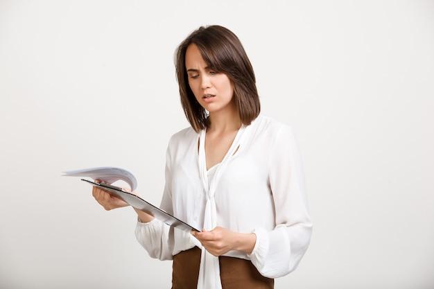 Documento de leitura de mulher confusa Foto gratuita