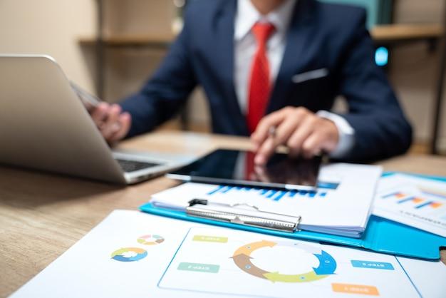 Documentos de negócios na mesa de escritório com telefone inteligente e tablet digital Foto Premium